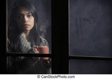 Portrait of a beautiful woman behind window with a cup of coffee