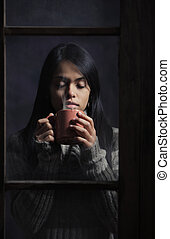 Young woman behind window with a cup of coffee or tea, focus...