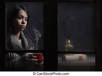 Woman behind wet window with a cup of coffee or tea
