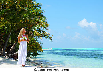 woman with a coconut cocktail on a tropical shore
