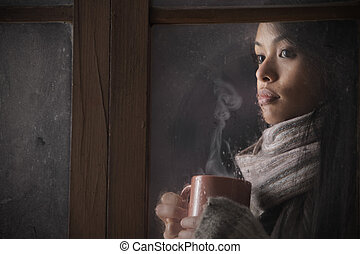 Portrait of a beautiful woman behind window with a cup of...
