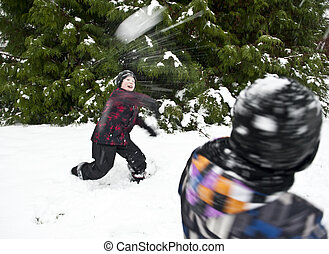 Throwing snowball - Children playing outdoors at wintertime...