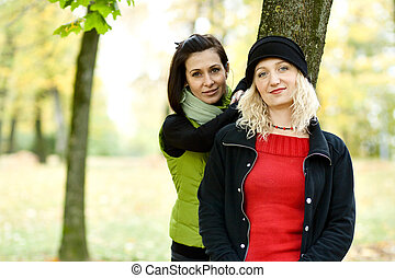 Two young women in autumn park