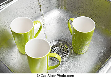 Washing green cups in the kitchen sink - Washing bright...