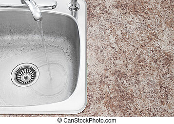 Water running from kitchen faucet and countertop detail -...