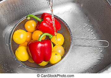 Washing colorful fruits and vegetables in the kitchen sink.