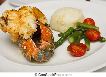 Lobster Tail with Vegetables - A lobster tail on plate with...