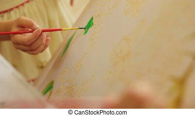 Batik technique - Two people drawing on textile. Batik...