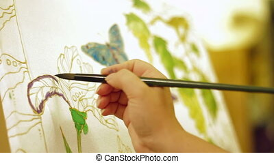 Wax printing - Person painting an image using batik...