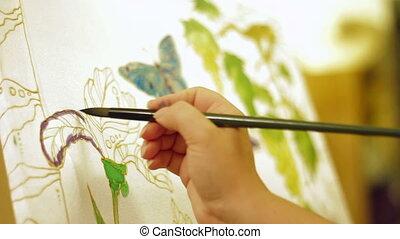 Wax printing - Person painting an image using batik...