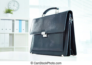Briefcase - Image of black leather briefcase on desk in...