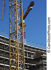 cranes and scaffolding during construction of a building on...