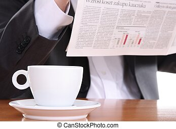Businessman reading newspaper and drinking coffee, business...