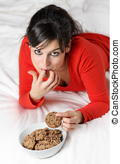 Playful woman breaking diet and eating cookie - Young woman...