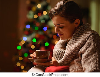 Dreaming young woman sitting chair with hot chocolate in...