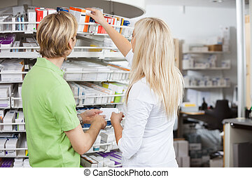 Pharmacy Lifestyle - Two pharmacists filling drug...