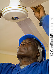 Construction Worker Fixing Ceiling Fan - African American...