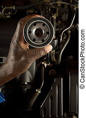 South African or American hand holding oil filter with...