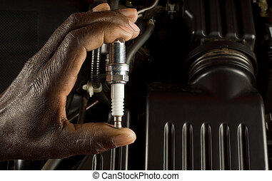 South African or American hand holding car spark plug with...