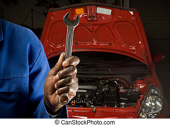 South African or American mechanic with spanner in front of...