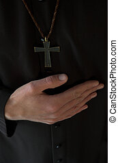 Hands below crucifix - Priest hand below crucifix on black...