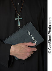 Priest, cross and bible - Priest holding bible with crucifix