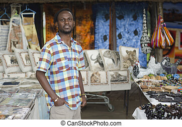 african curio salesman vendor in front of wildlife items -...