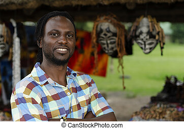 African curio salesman vendor in front of ethnic masks -...