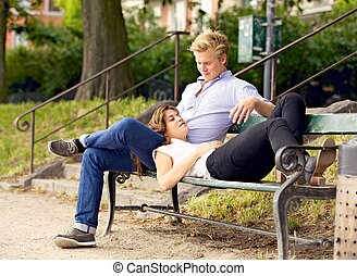 Man Looking at His Girlfriend Resting on His Lap - Sitting...