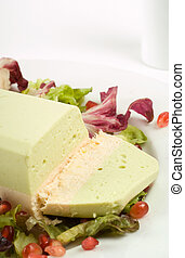 Salmon and avocado terrine on white plate with salad