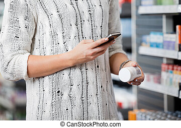 Woman Scanning Bottle with Smart Phone - Detail of woman...