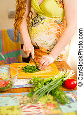 pregnant woman s hands and belly cutting on kitchen with...
