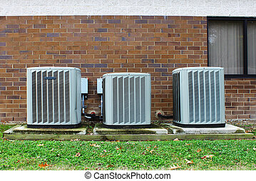 A group of three industrial sized air conditioners along a...
