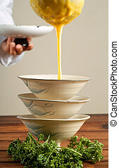 Chef pouring butternut soup - Chef puring butternut soup in...