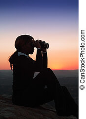 Silhouette of Business Woman with Binoculars Sitting on a...