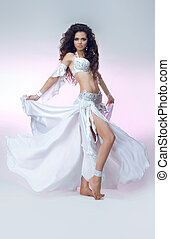 Young dancing girl with smart fair hair in Oriental shining costume. Beautiful slim woman belly dancer.