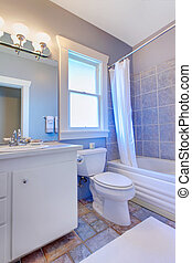 Blue bathroom with white cabinets with stone tiles and blue...