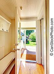Beige walls hallway with open door and hardwood floor -...