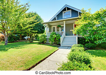 Grey small old American house front exterior with white staircase.