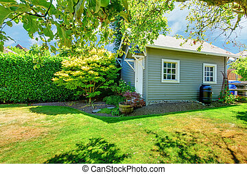 Small grey shed in the sunny green backyard.