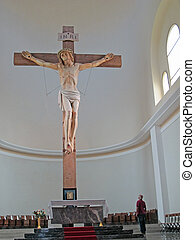 great huge wooden crucifix inside a church and a man