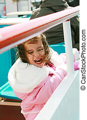 playful pretty little girl excited recreating in a ride on sail boat enjoying the spring