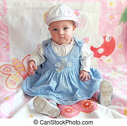 Adorable baby girl sitting in beautiful blue dress and funny...