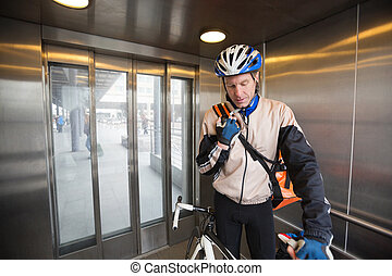 Male Cyclist With Courier Bag In An Elevator - Young male...