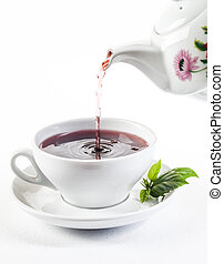 Pouring fresh tea in to white cup