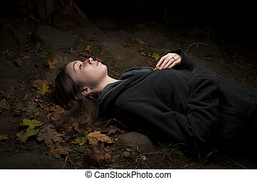 Attractive woman lying in autumn leaves - Attractive woman...