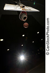 Basketball hoop and ball in midair at night with lights...