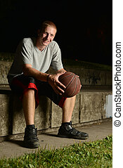 Smiling basketball player sitting down to rest, while...