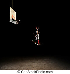 Nighttime basketball player - Basketball court at night with...