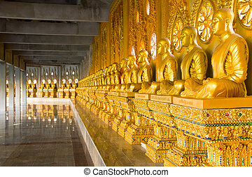 row of golden monk buddhist statues in thai temple,...
